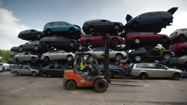 wide shot of a man in a forklift vehicle driving past stacked cars at a scrapyard, uk. - altmetall stock-videos und b-roll-filmmaterial