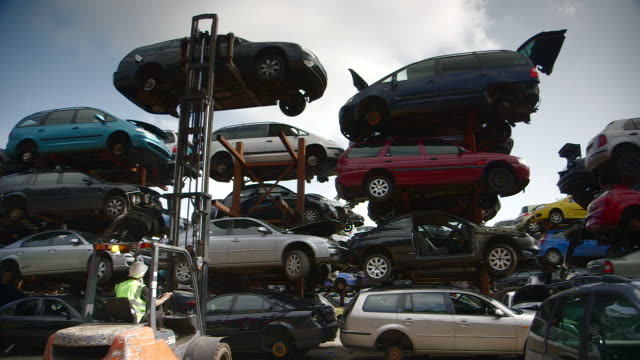 Wide shot of a man using a forklift vehicle to move an old car to the top tier of a storage rack at a scrapyard, UK.