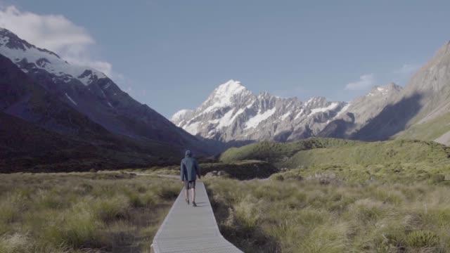 vídeos de stock, filmes e b-roll de tiro largo de um homem se afastando da câmera em um vale na nova zelândia - 1 minuto ou mais
