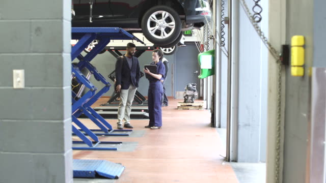 Wide shot of a mechanic talking to a client