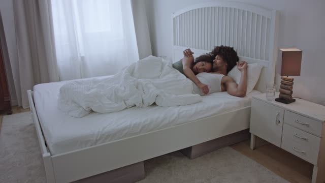 stockvideo's en b-roll-footage met wide shot of a mid adult heterosexual love couple waking up together at home in the morning. - dubbel bed