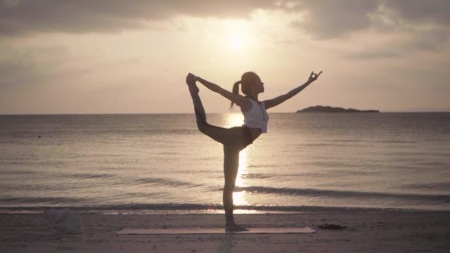 遠隔地のビーチでヨガを練習するミレニアル世代の女性のワイドショット - ヨガ点の映像素材/bロール