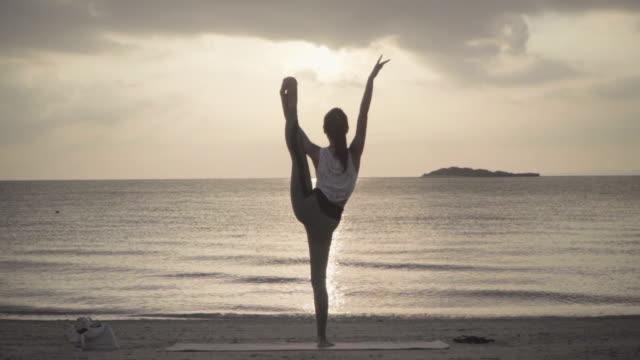 遠隔地のビーチでヨガを練習するミレニアル世代の女性のワイドショット - yoga点の映像素材/bロール