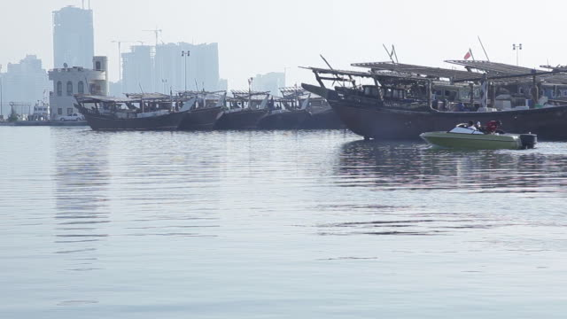 wide shot of a motorboat crossing traditional fishing dhows moored in a marina. manama skyline in the background. - ダウ船点の映像素材/bロール