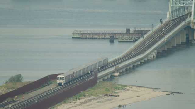 Wide shot of a NYC subway 'A' train moving over a hump bridge in Queens
