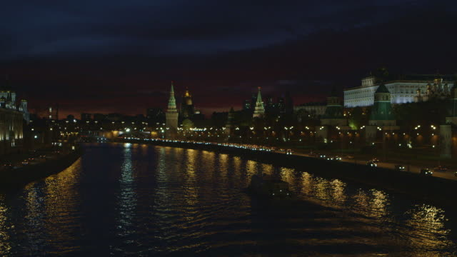 Wide shot of a passenger boat travelling past the Kremlin during a beautiful sunset in Moscow, Russia.