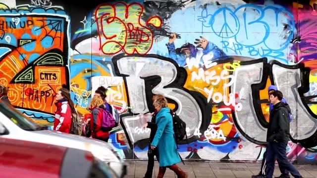 wide shot of a people walking past street art on the side of a building in stokes croft bristol uk no - bristol england stock videos & royalty-free footage