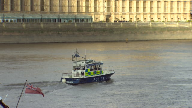 wide shot of a police boat moving along the thames past the houses of parliament - police boat stock videos and b-roll footage