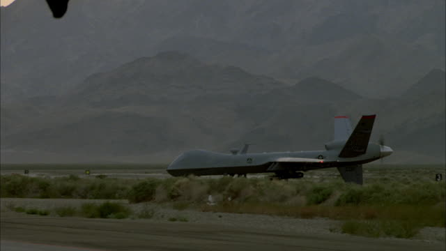 wide shot of a predator drone taxing on the runway of a rural airfield. - armed forces stock videos & royalty-free footage