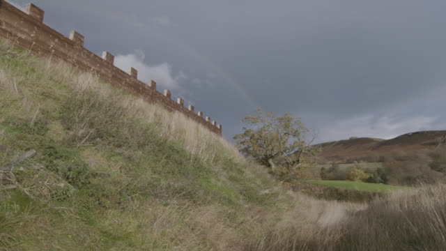 wide shot of a reconstructed wooden wall at the vindolanda roman fort with a rainbow in the background - uncultivated stock videos & royalty-free footage
