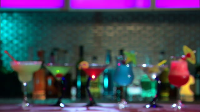 stockvideo's en b-roll-footage met wide shot of a row of tropical drinks on a bar, rack focusing to a blurred background. - martiniglas