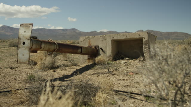 wide shot of a ruined structure in a desert at nevada test site - massenvernichtungswaffe stock-videos und b-roll-filmmaterial