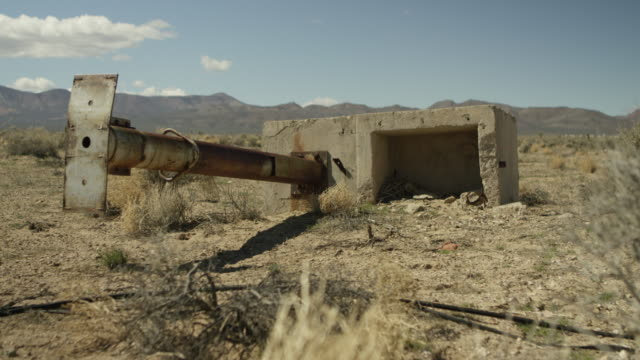 wide shot of a ruined structure in a desert at nevada test site - weapons of mass destruction stock videos and b-roll footage