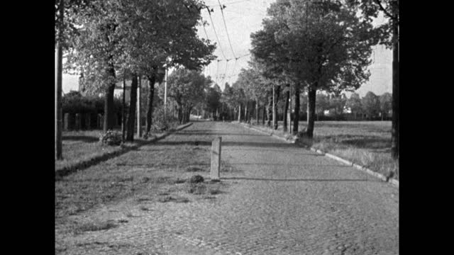 wide shot of a rural road that straddles the east/west germany border; 1959. the eastern side is overgrown with grass, the western side is... - 1950 1959 stock videos & royalty-free footage