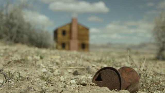 vidéos et rushes de wide shot of a rusty can in front of a house at nevada test site - arme de destruction massive