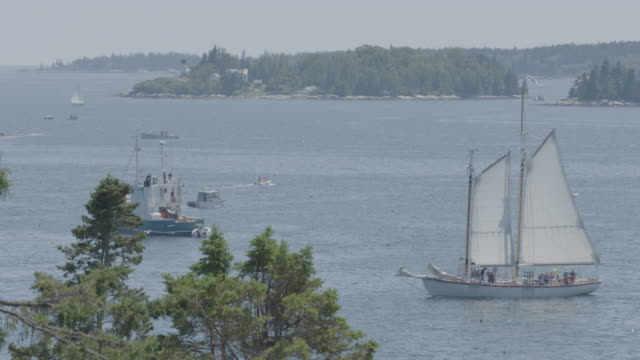 Wide shot of a sailboat passing by in Boothbay Harbor