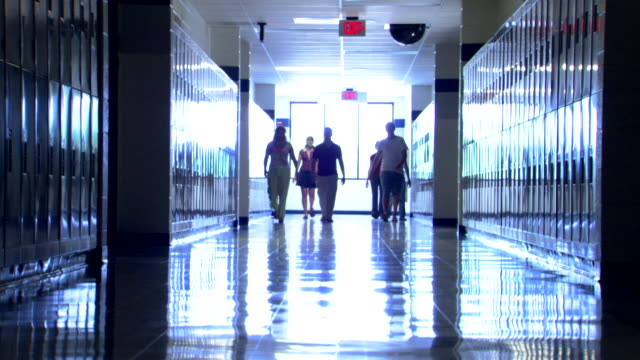 Wide shot of a school hall as students come around a corner and walk toward and past the viewer.