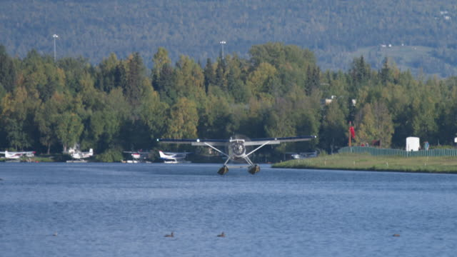 Wide shot of a seaplane landing on the water