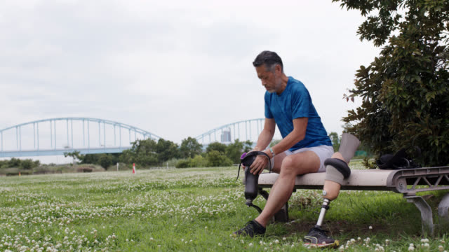 wide shot of a senior adaptive athlete affixing his running blade - prosthetic equipment stock videos & royalty-free footage