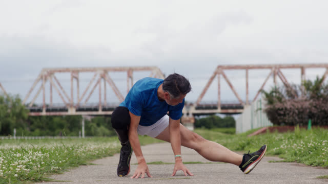 vídeos y material grabado en eventos de stock de amplia toma de un corredor amputado senior que se estira antes de una carrera - diversidad funcional