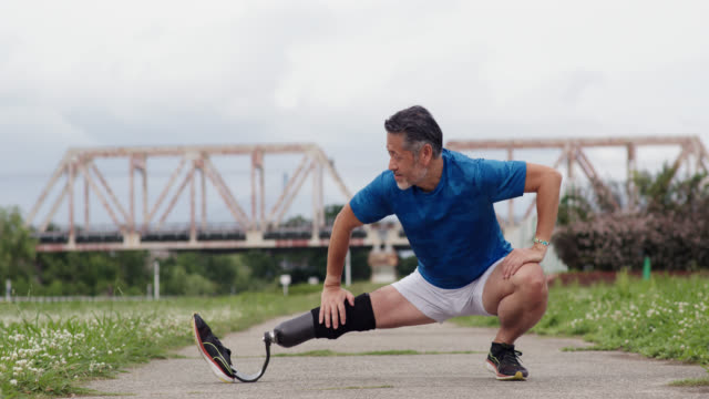 wide shot of a senior amputee runner stretching before a run - artificial limb stock videos & royalty-free footage