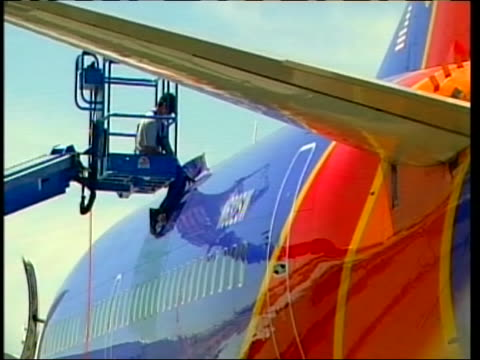 wide shot of a southwest worker inspecting top of a plane. this after another southwest plane made an emergency landing in yuma, arizona on april 1,... - südwesten stock-videos und b-roll-filmmaterial