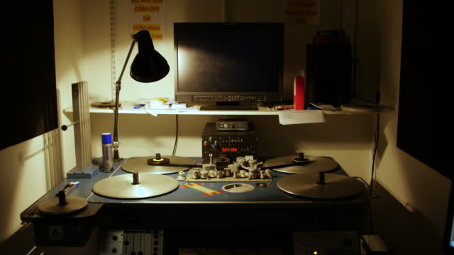 Wide shot of a 'Steenbeck' flatbed film editor and monitor displaying a 'countdown'
