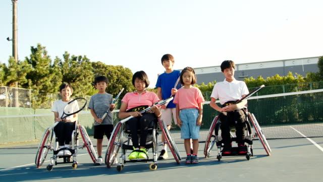vídeos de stock, filmes e b-roll de slo mo tiro largo de uma equipe de tenistas adaptativos falando - cadeira de rodas equipamento ortopédico