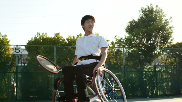slo mo wide shot of a teenage adaptive athlete in a wheelchair playing tennis - drive ball sports stock videos & royalty-free footage