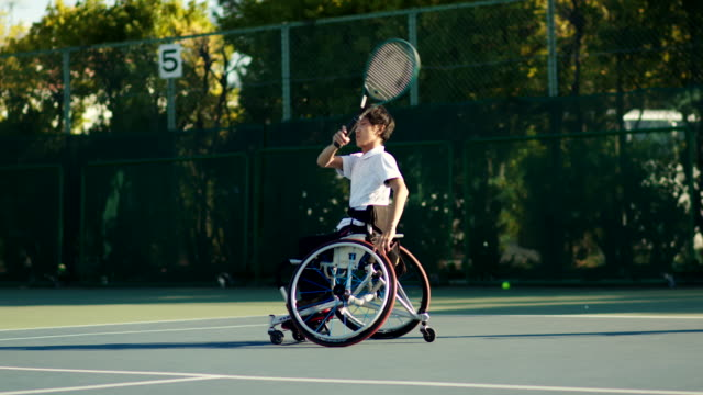 slo mo wide shot of a teenage adaptive athlete playing tennis - drive ball sports stock videos & royalty-free footage