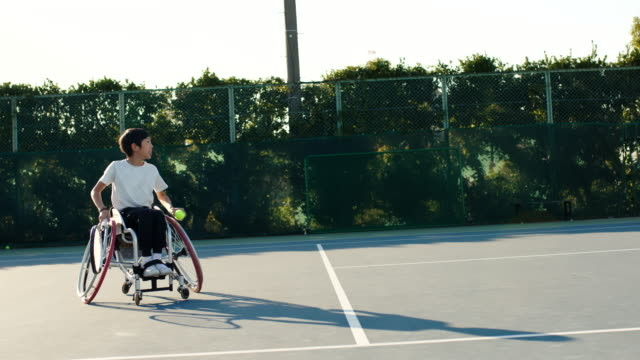 slo mo wide shot of a teenage adaptive tennis player serving - drive ball sports stock videos & royalty-free footage