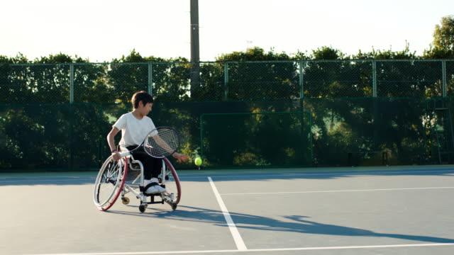 10代のアダプティブテニスプレーヤーのslo moワイドショット - テニス点の映像素材/bロール
