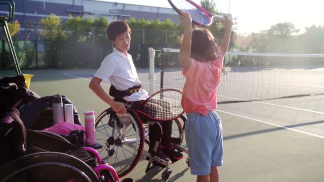 若い選手と話している10代のアダプティブテニスプレーヤーのワイドショット - 身体障害点の映像素材/bロール
