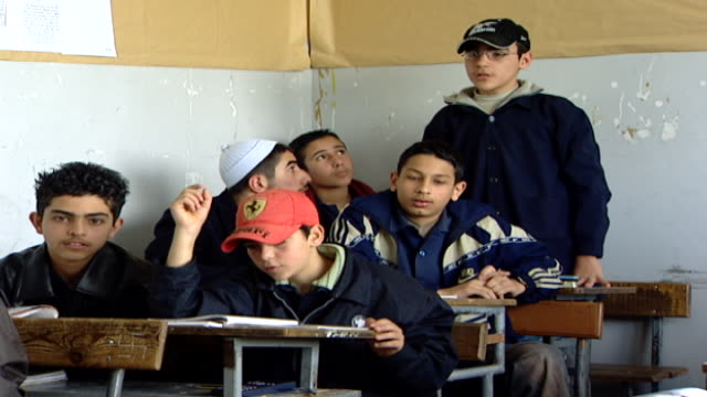 wide shot of a teenage boy standing at the back of a classroom, answering a question. irfan is a druze religious school with five branches across... - シャイフ点の映像素材/bロール