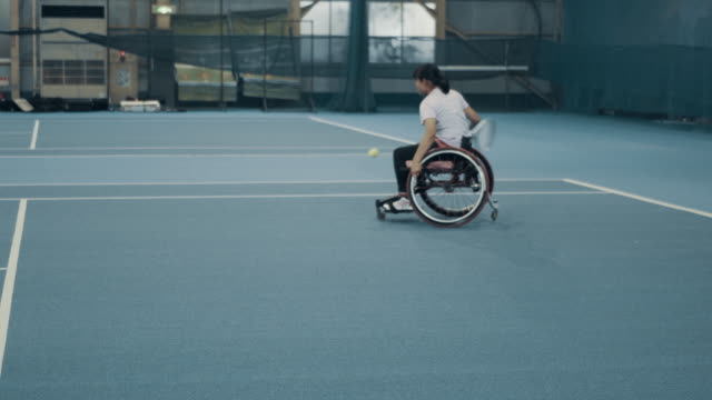 wide shot of a teenage girl playing wheelchair tennis - disability stock-videos und b-roll-filmmaterial