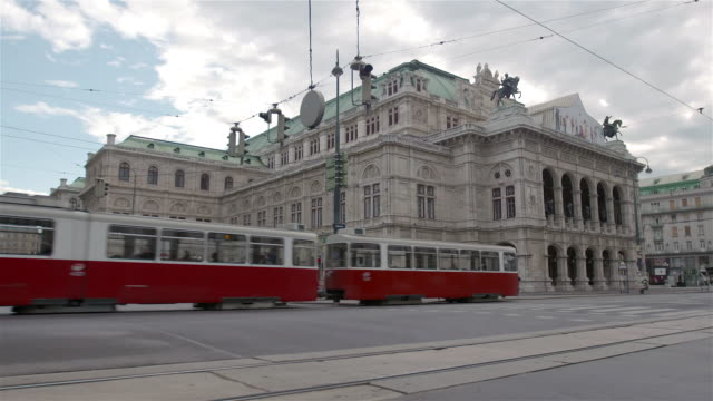 Wide shot of a tram passing the Vienna State Opera House, Austria.