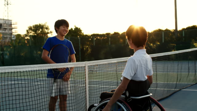 slo mo wide shot of a two friends talking centre court after a game of tennis - drive ball sports stock videos & royalty-free footage