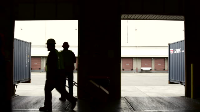 Wide shot of a warehouse worker rolling up a door