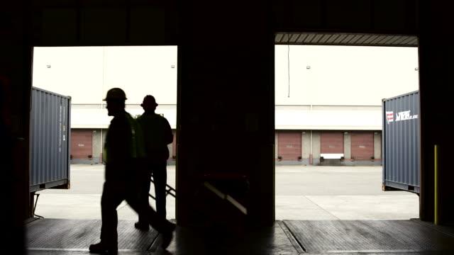 wide shot of a warehouse worker rolling up a door - 倉庫作業員点の映像素材/bロール