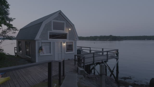 Wide shot of a waterfront house in Boothbay Harbor early in the evening