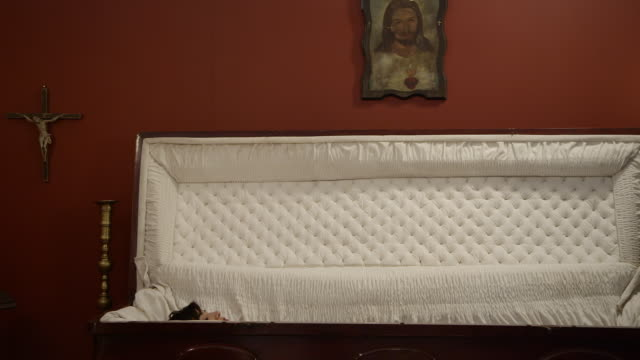 vidéos et rushes de wide shot of a woman rising from the dead in her coffin - cercueil