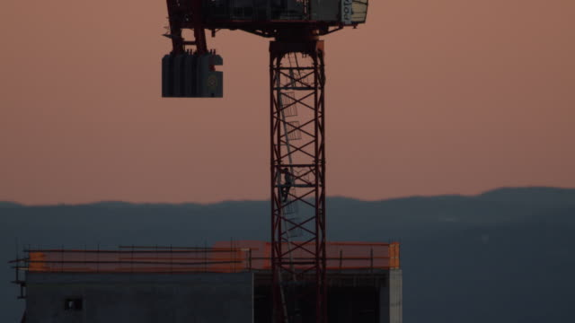 Wide shot of a worker climbing up a rooftop crane at the 3 World Trade Center construction site during sunrise