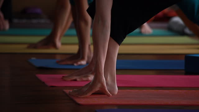 wide shot of a yoga class on an outside yoga deck surrounded by lush vegetation and then zoomed into a medium shot of women putting their hands on yoga mats - kelly mason videos stock videos & royalty-free footage
