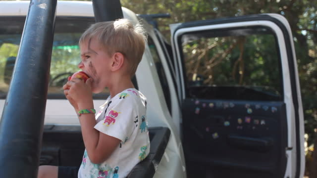 wide shot of a young boy eating a peach on the back of a pickup truck on a summer day. - kelly mason videos video stock e b–roll