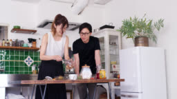 Wide shot of a young couple making granola breakfast together in the kitchen