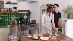 Wide shot of a young couple preparing dinner at home together