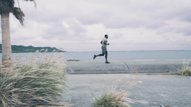 若い男がスローモーションで海岸沿いのジョギングのワイド ショット - side view点の映像素材/bロール
