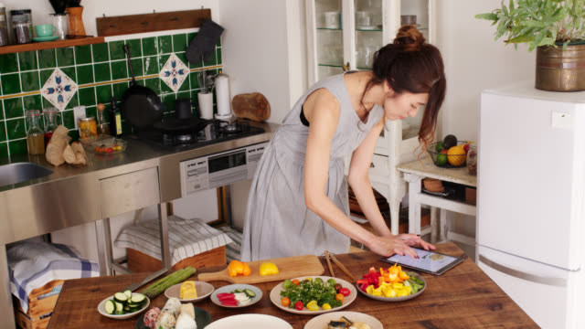 wide shot of a young woman cooking using digital tablet for recipe - preparing food stock videos & royalty-free footage