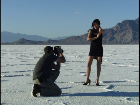 wide shot of a young woman in a black dress as she smiles and poses for a photographer in a desert