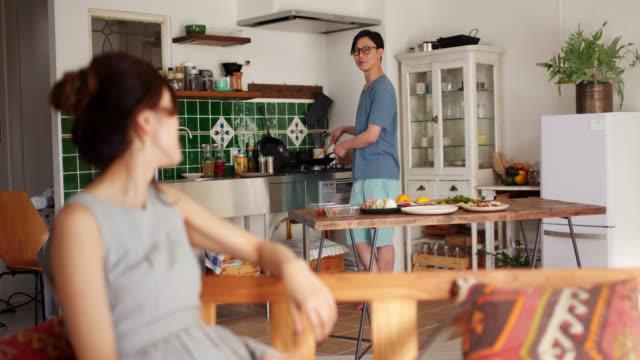 ラップトップを使用して、彼はバックグラウンドで調理している間、彼女の彼氏に話している若い女性のワイドショット - 若いカップル点の映像素材/bロール